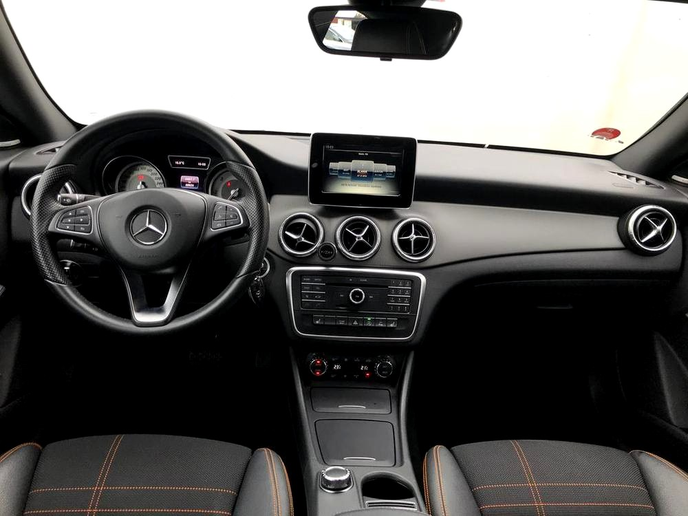 Červený Mercedes-Benz CLA 2.2 CDi, rok 2015, interiér vozu v černé barvě, pohled na palubní desku, s pro mercedes typyckými kulatými výdechy klimatizace, volant a středový panel