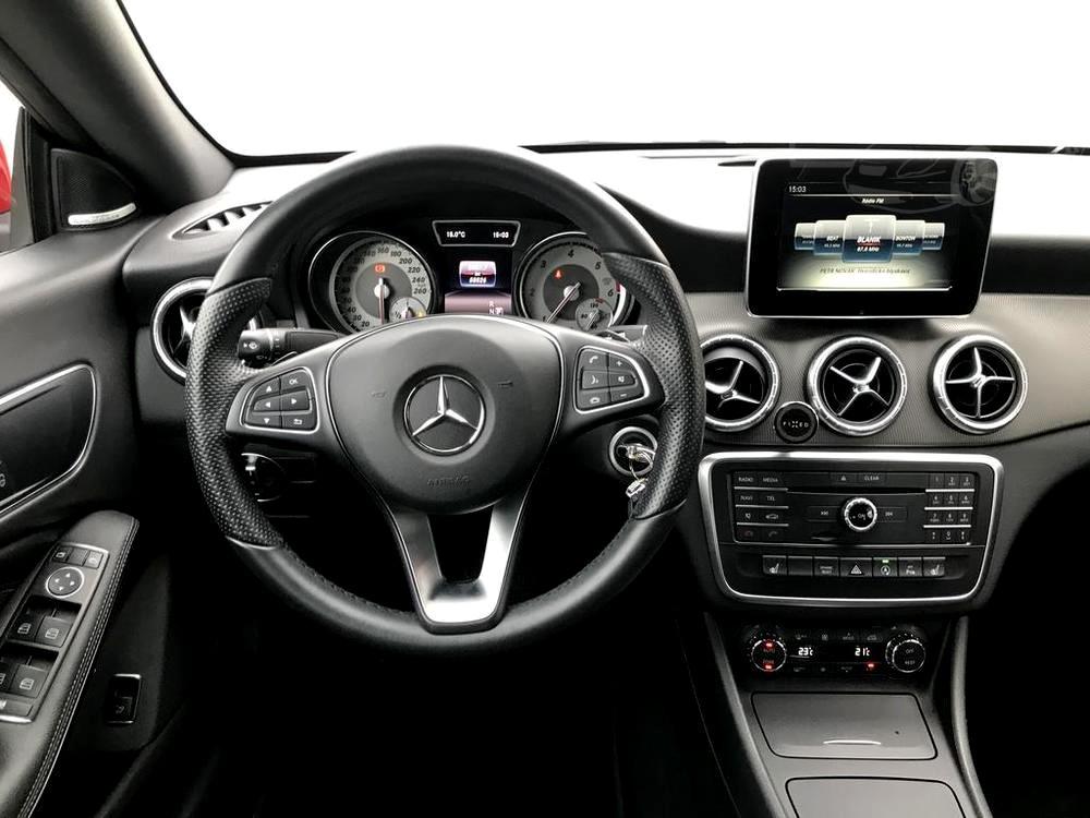 Červený Mercedes-Benz CLA 2.2 CDi, rok 2015, interiér vozu v černé barvě, pohled na přední dveře, palubní desku, kulaté výdechy klimatizace, detaily volantu, budíky a středový panel