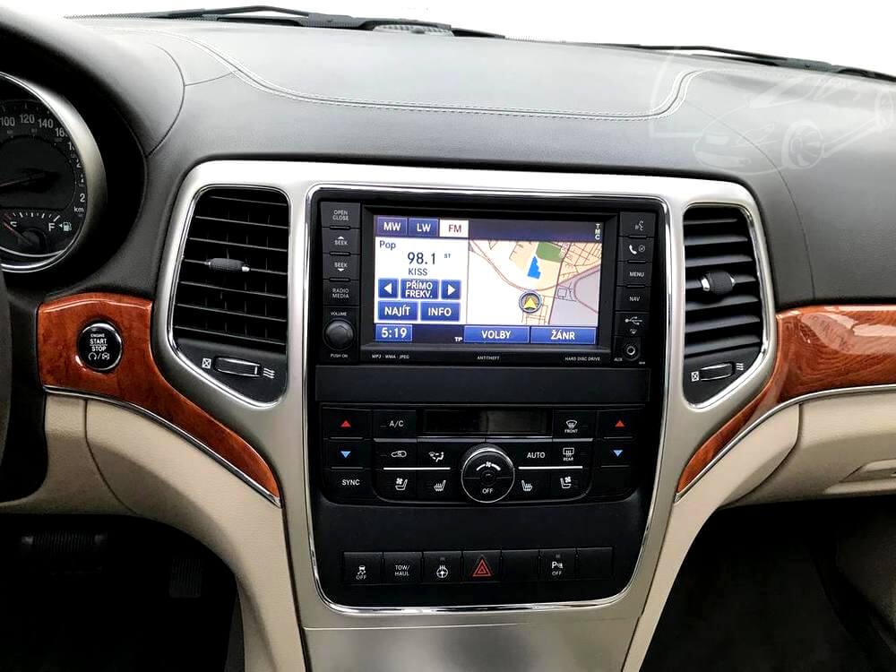 Středový panel s palubním PC, rádiem, automatickou dvouzónovou klimatizací, obložený dřevem a světlou kůží.